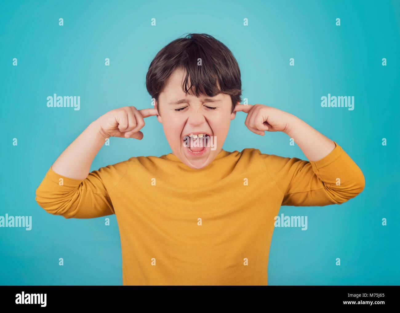 Porträt von einem schreienden kleinen Jungen, die Ohren mit den Händen Stockbild