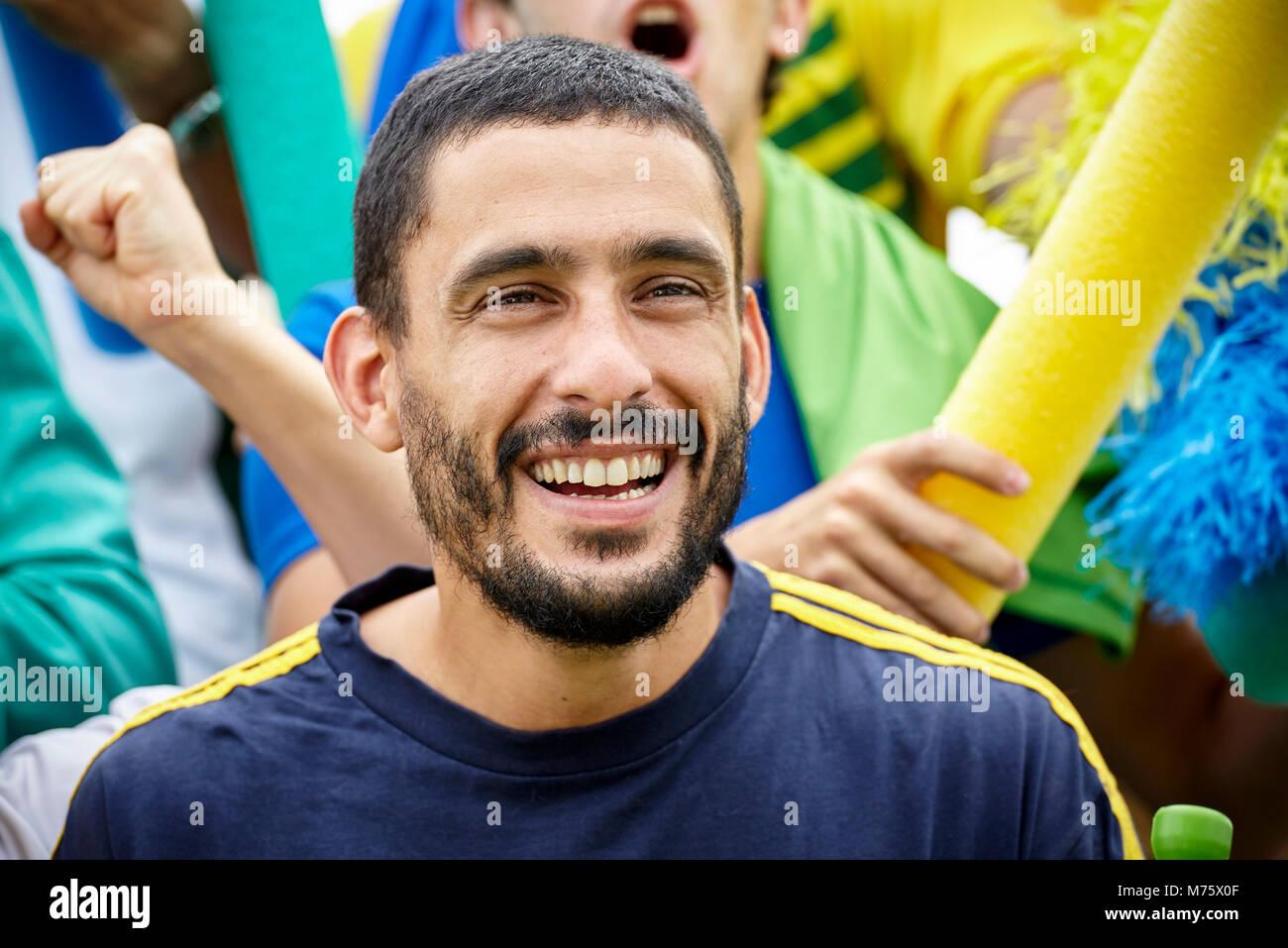 Mann fröhlich lächelnd an Fußballspiel, Porträt Stockbild