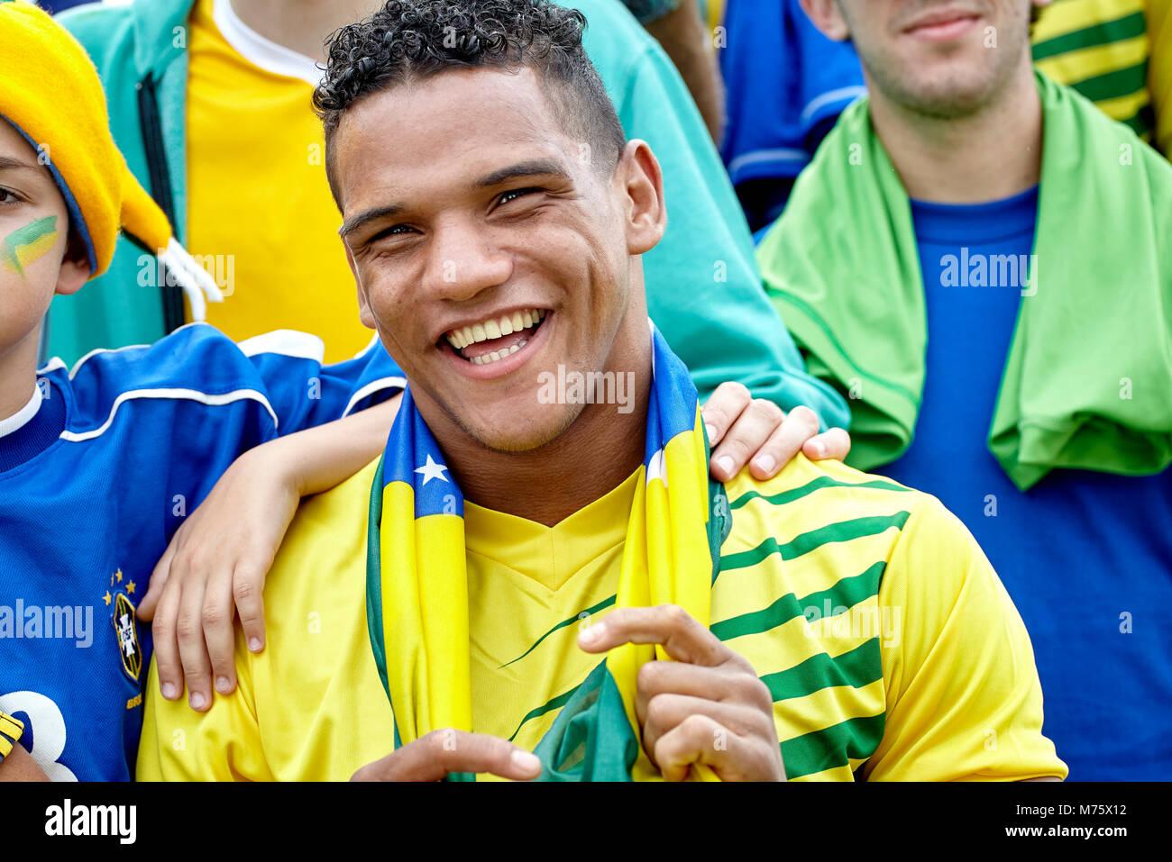 Brasilianischen Fußball-Fan freundlich lächelnd an überein Stockbild