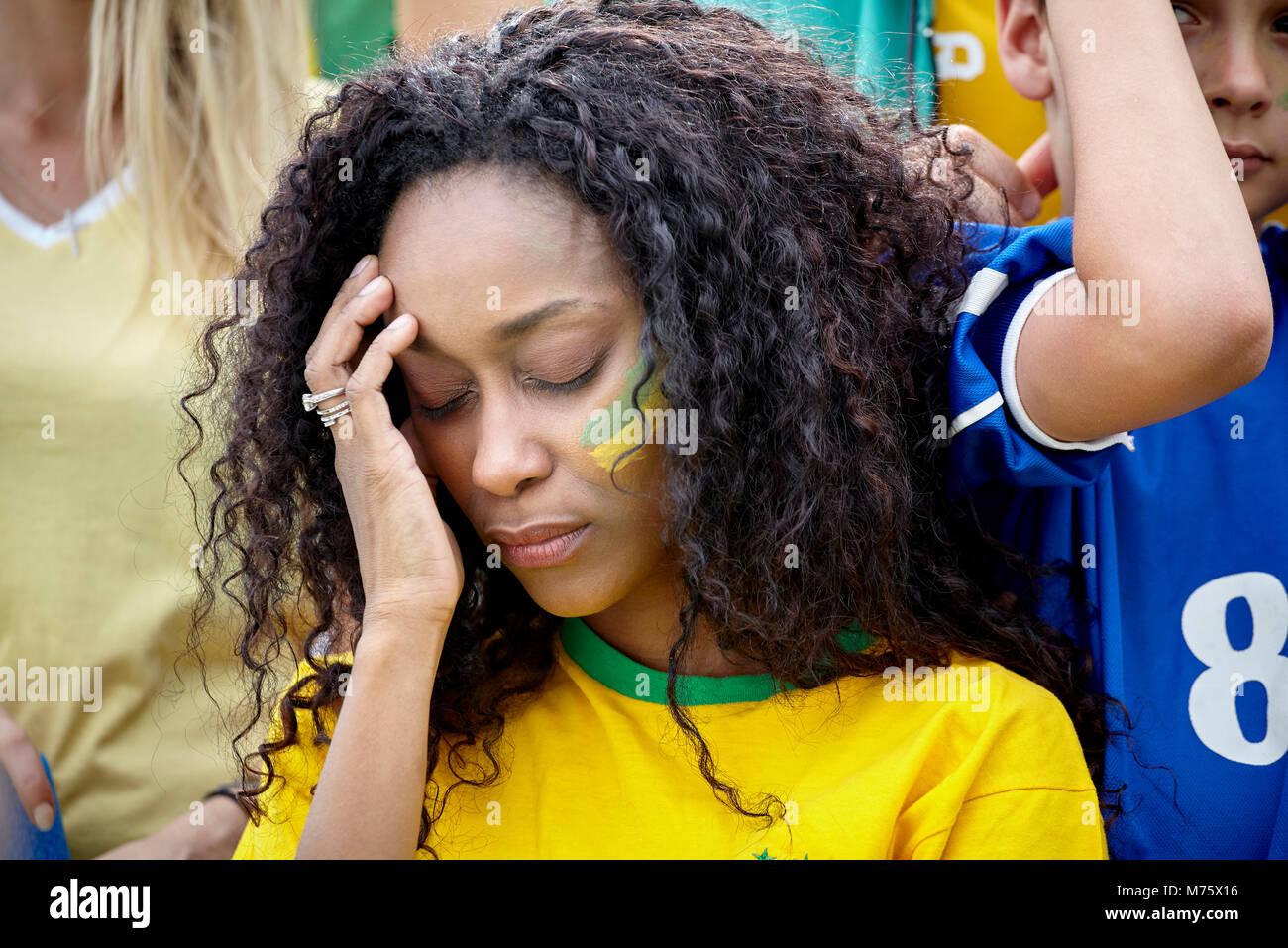 Frau mit Kopf in Enttäuschung bei brasilianischen Fußball Stockbild
