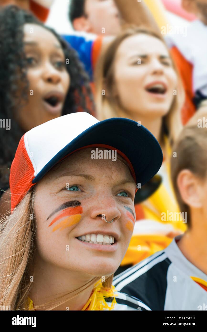 Deutsche Fußballfans beobachten mit Gesicht zur Unterstützung lackiert Stockbild