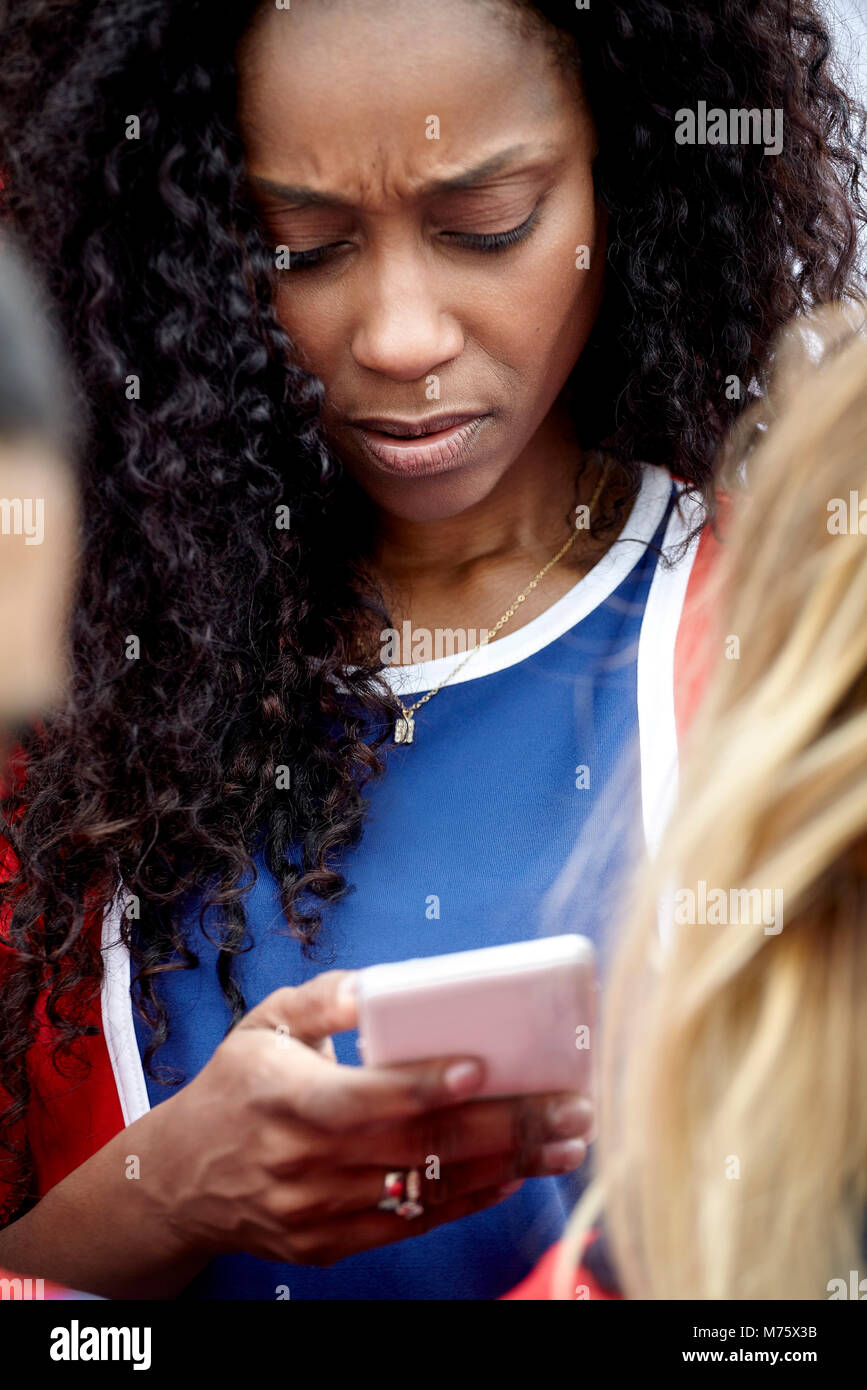 Frau Suchen bei Smartphones mit Sorge Ausdruck auf dem Gesicht Stockbild