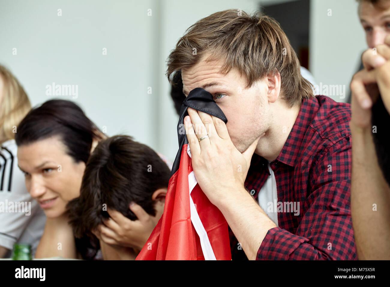 Deutsche Fußball-Anhänger für Gesicht mit Flagge während Gleiches zu Hause beobachten Stockbild
