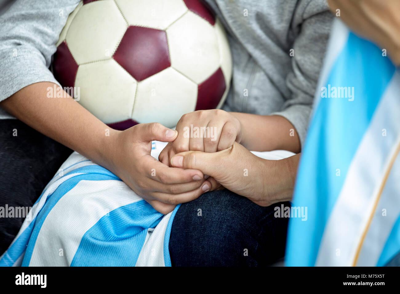 Kind holding Fußball, 7/8 Stockbild