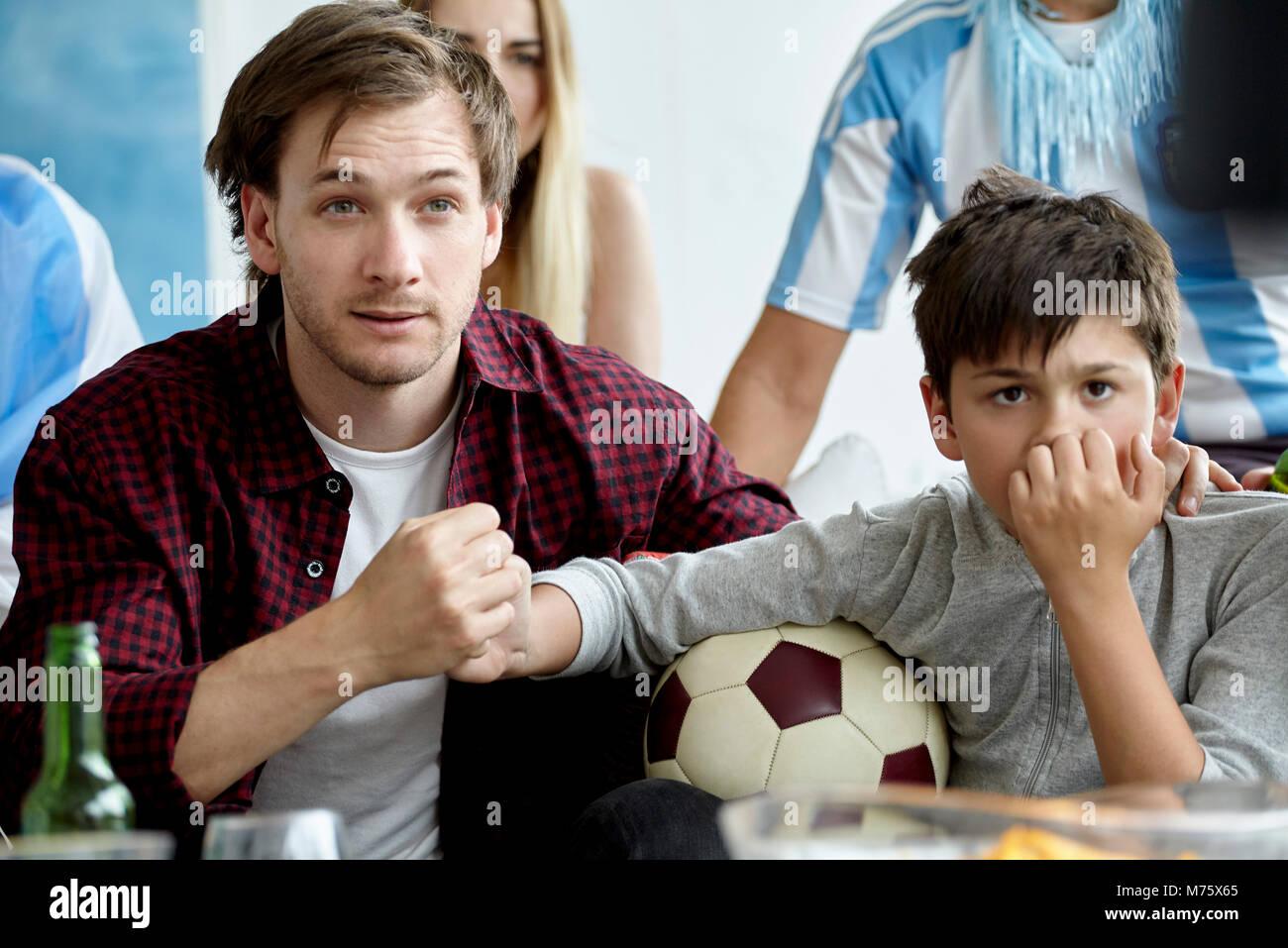 Vater und Sohn halten sich an den Händen, während Sie Fußballspiel zu Hause Stockbild