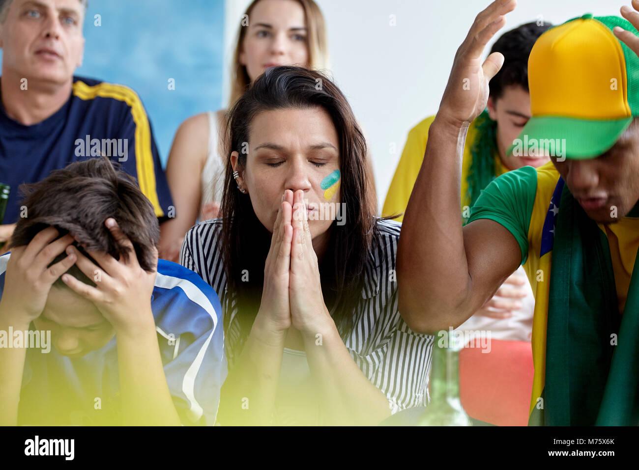 Brasilianischen Fußball-Fans auf der Suche umgekippt während Gleiches zu Hause beobachten Stockbild