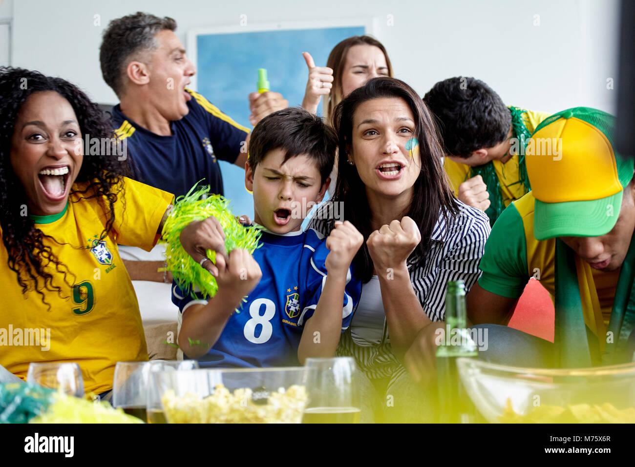 Brasilianischen Fußball-Fans feiern Sieg während Gleiches zu Hause beobachten Stockbild