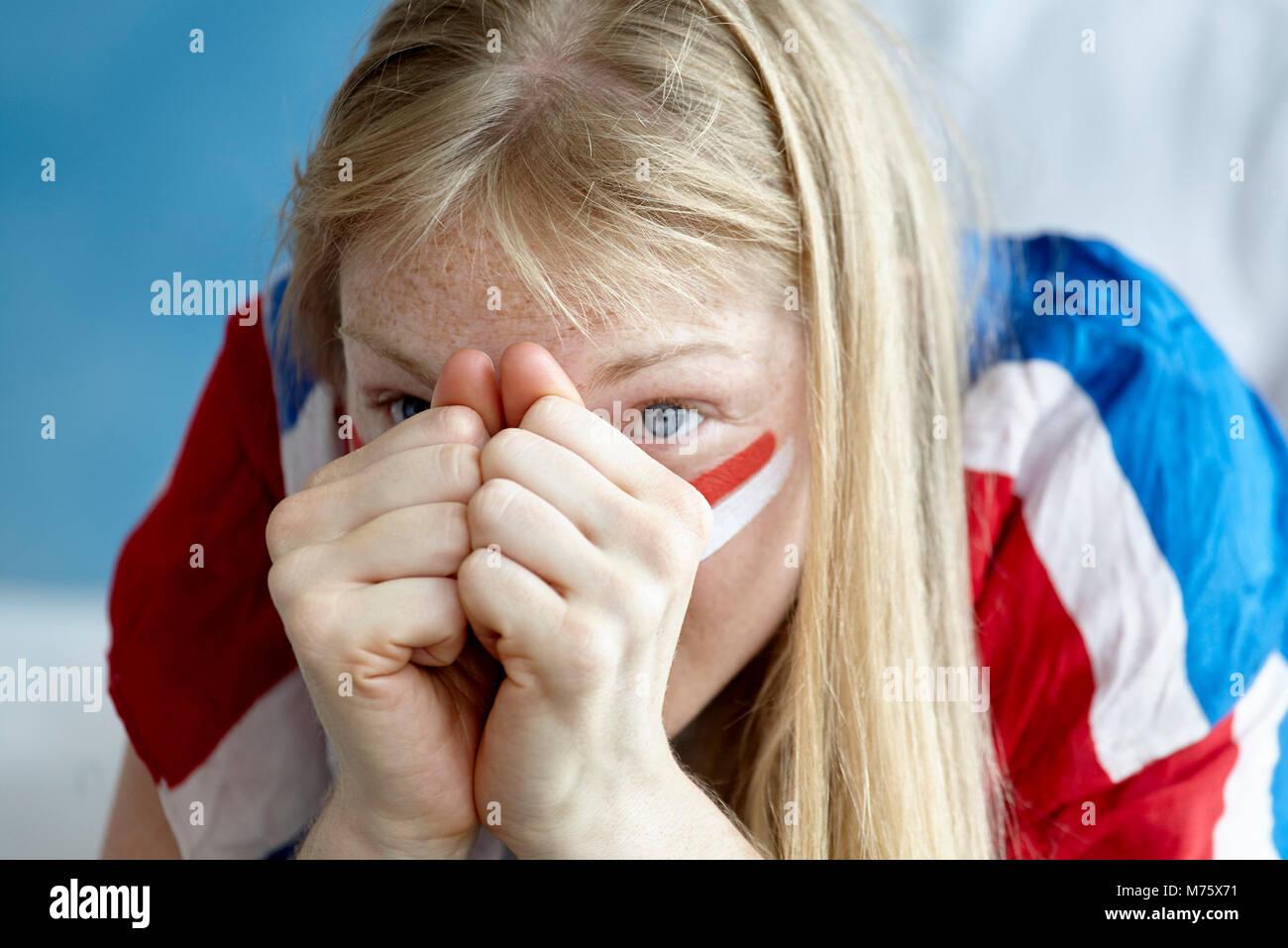 Sportenthusiasten ansehen Match mit gefalteten Händen zu Gesicht gespannt Stockbild