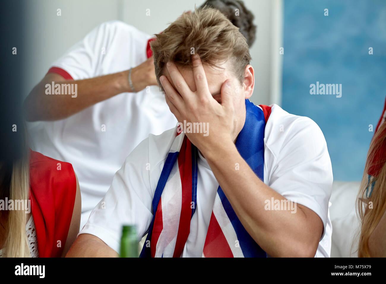 Britische Fußball-Fan das Gesicht mit der Hand während sie übereinstimmen Stockbild