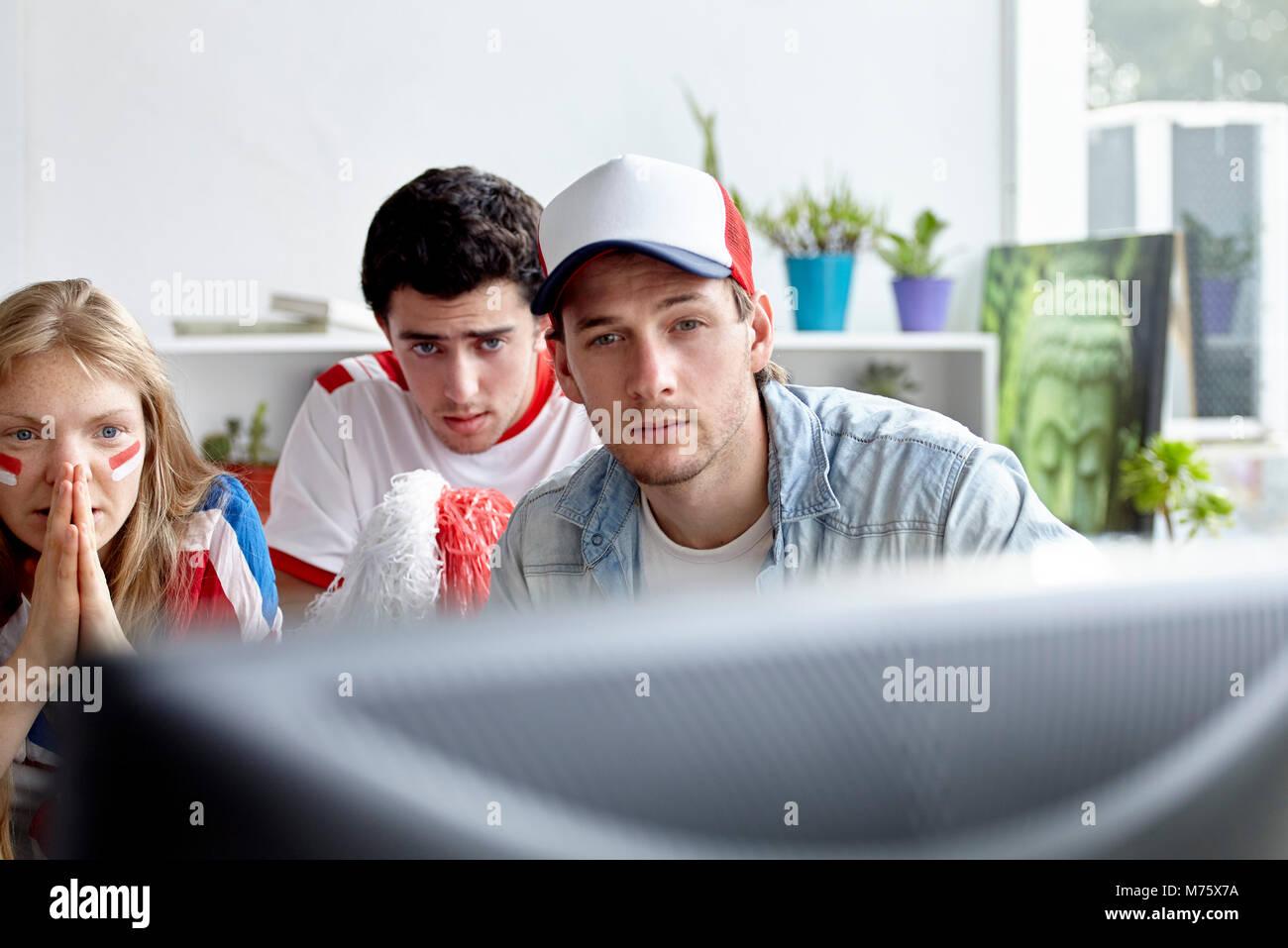 Sportbegeisterte beobachten Match auf TV zu Hause Stockbild