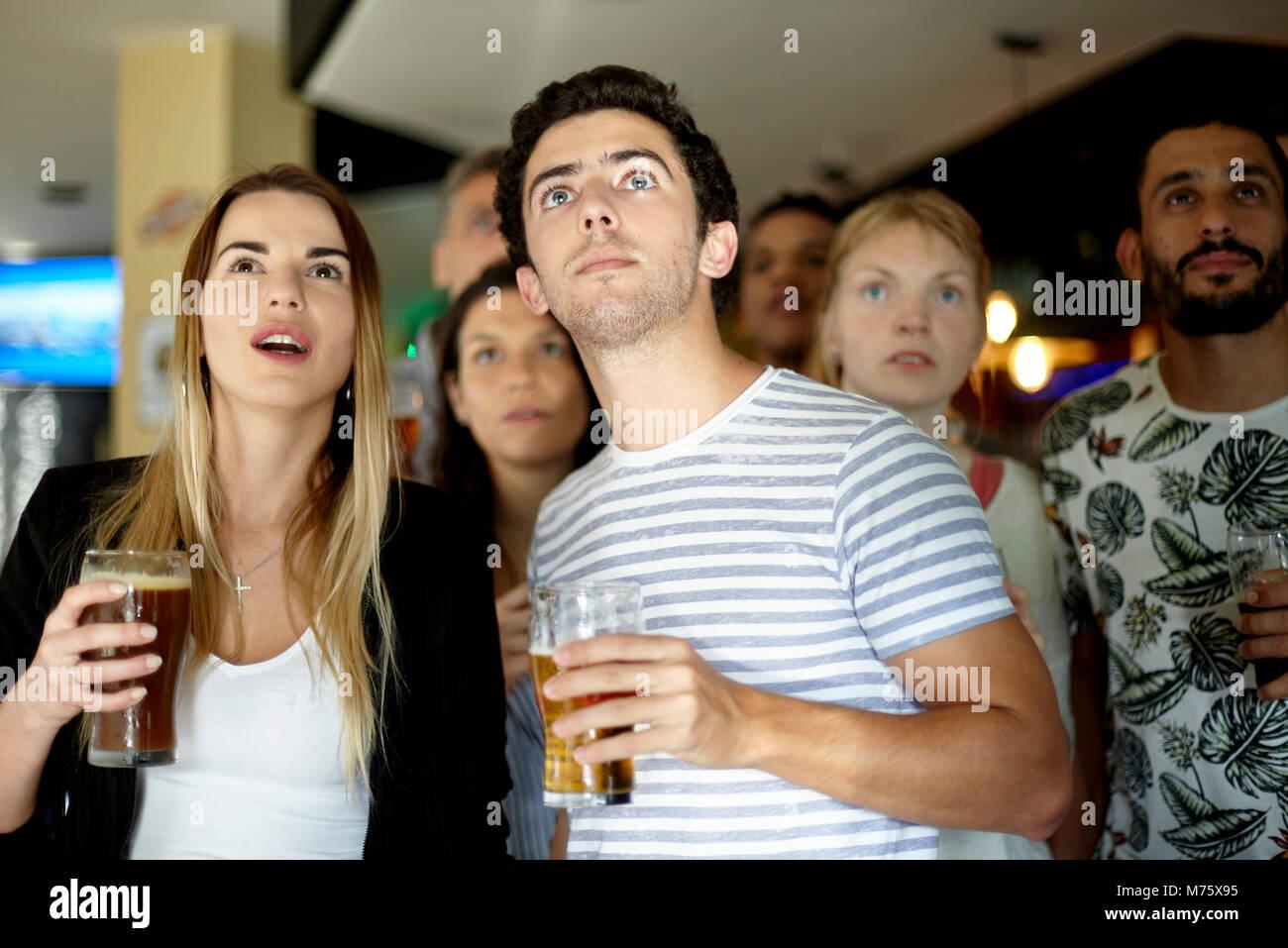 Sportbegeisterte beobachten Match in bar Stockbild
