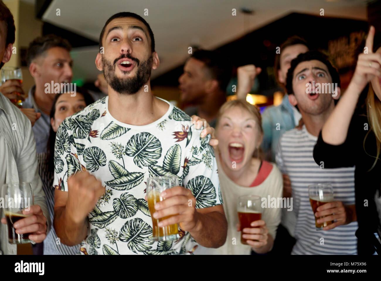 Sportbegeisterte aufgeregt beobachten Match in bar Stockbild