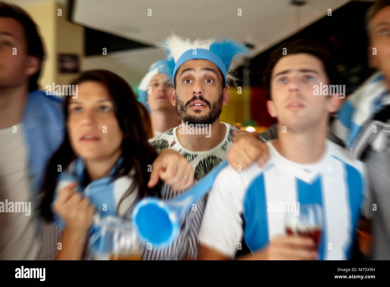Argentinische Fußball-Anhänger gespannt beobachten Match in bar Stockbild
