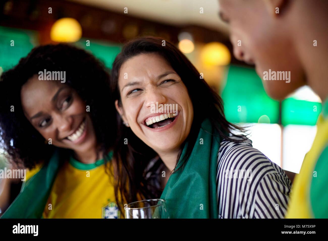 Frau lachend in der Bar mit Freunden Stockbild