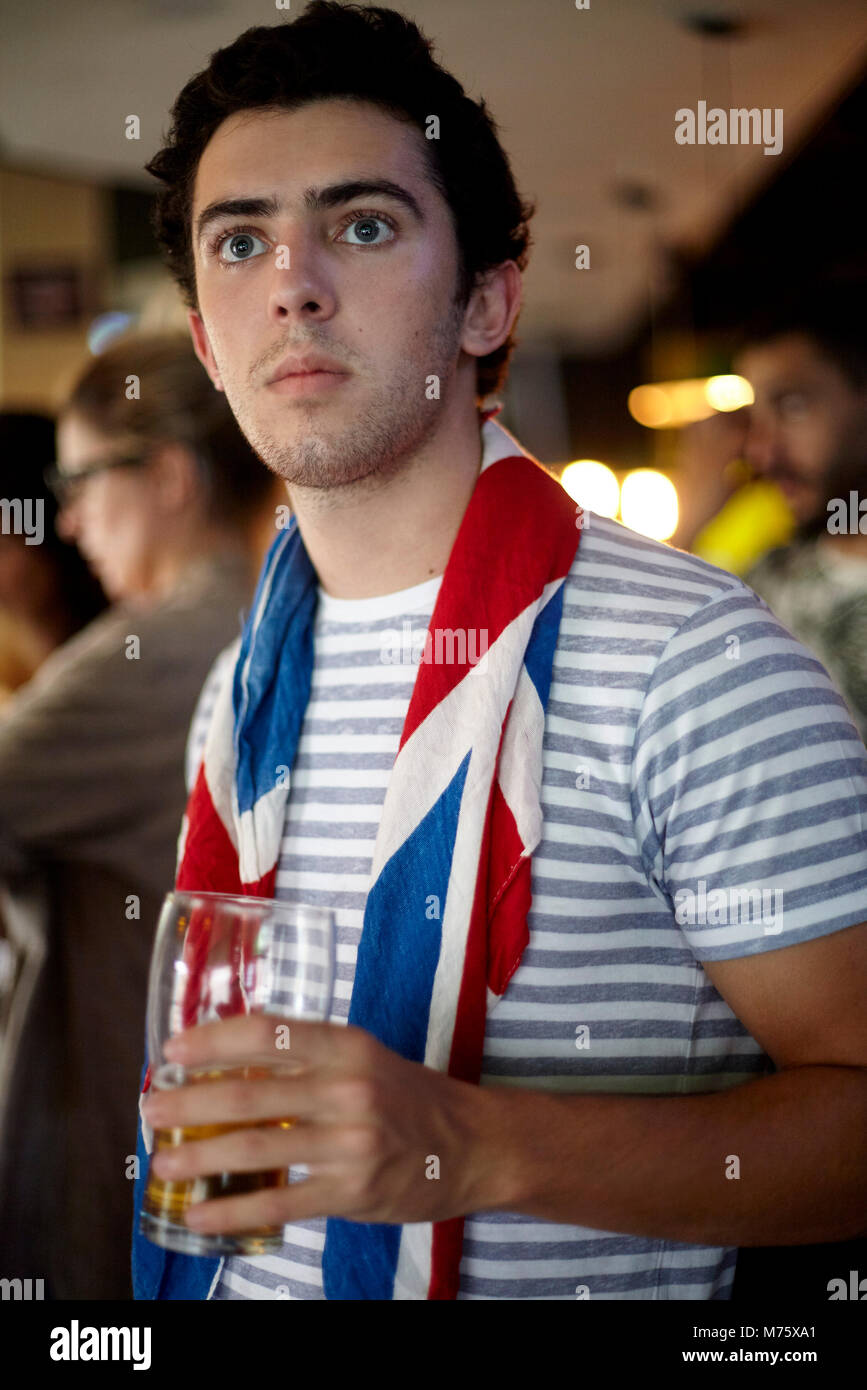 Britische Fußball-Fan ansehen Match in bar mit Flagge drapiert, um den Hals Stockbild