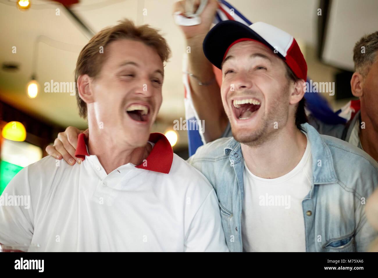 Sportbegeisterte Sieg feiern, während Sie in der Bar Stockbild