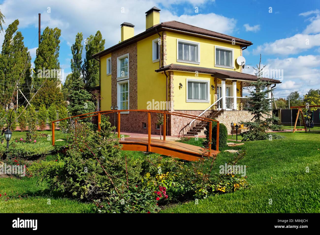 Die Außenseite Des Luxus Haus Mit Grünen Hof Und Hölzerne Brücke In Der  Landschaft Design