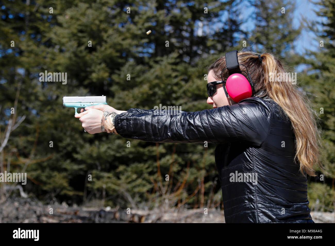 Frau schießen eine Pistole und die shell ist in der Luft. Stockbild