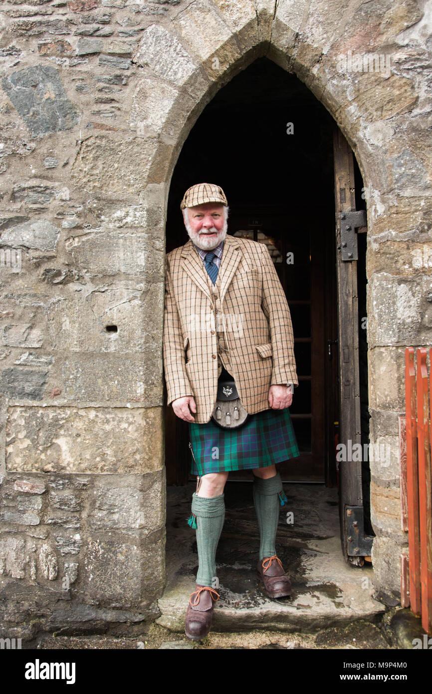 Portrait von reifer Mann in traditioneller Kilt lehnte sich auf torbogen von Eilean Donan Castle, Schottland, Großbritannien Stockbild