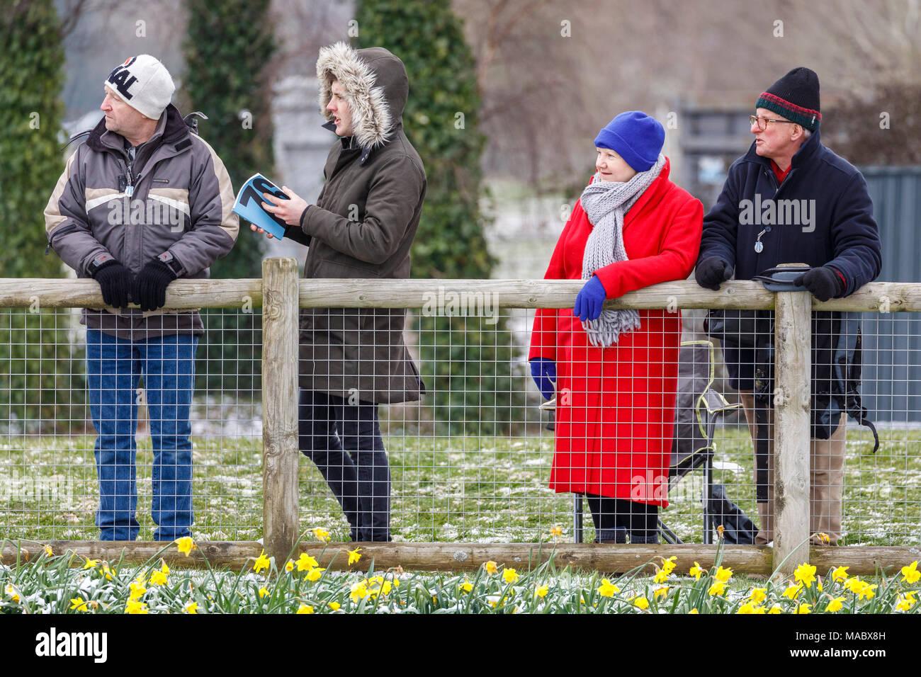 Kalt und Schweres beschichtetes Zuschauer an der Rennstrecke an der winterlichen Goodwood 76th Mitgliederversammlung, Sussex, UK. Stockbild