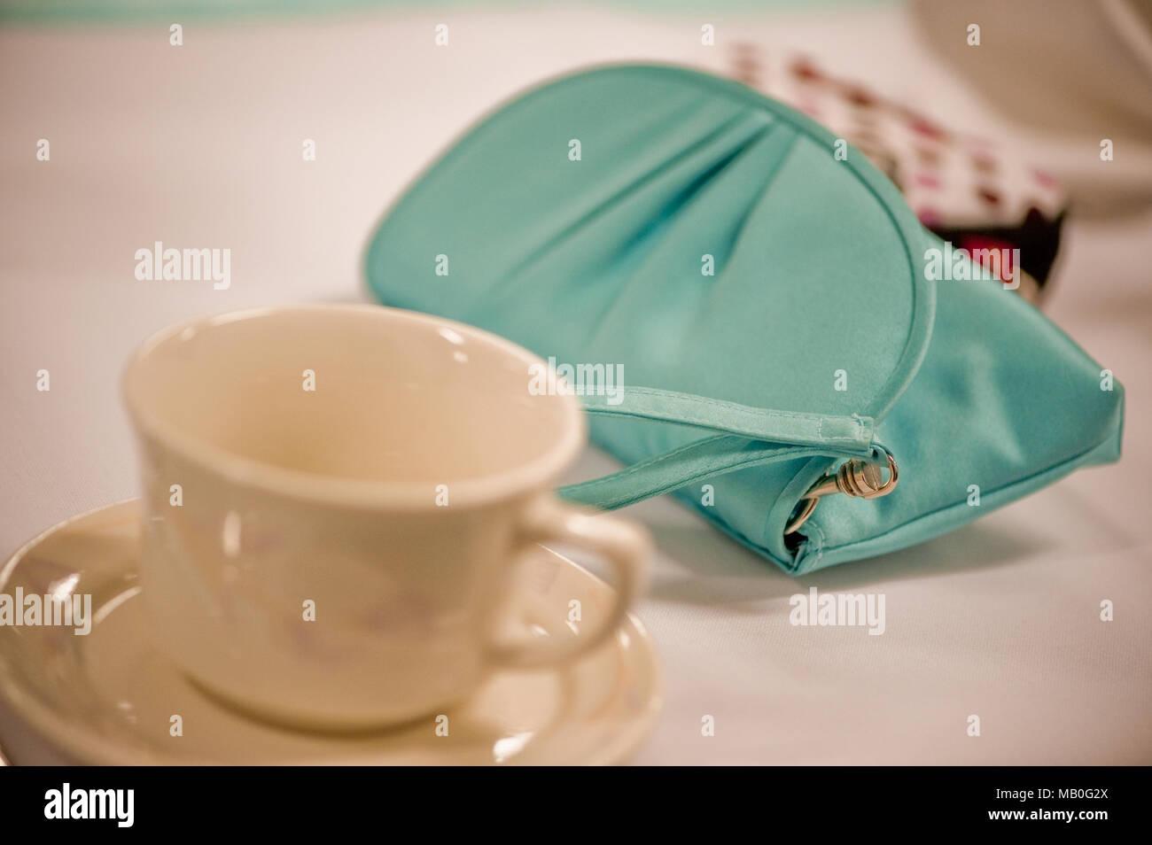 Eine kleine Teal farbige Geldbeutel neben einem leeren Tasse auf einem Tisch Stockbild