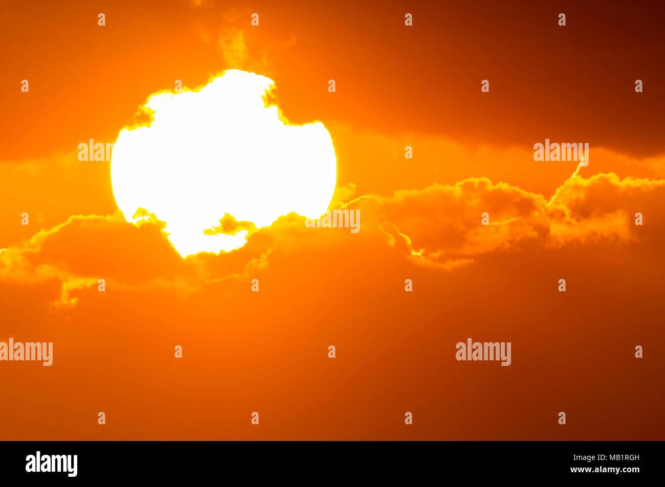 Detailansicht der glühenden Sonne, tief am Himmel, teilweise von Wolken bedeckt, kurz bevor es fest. Stockbild