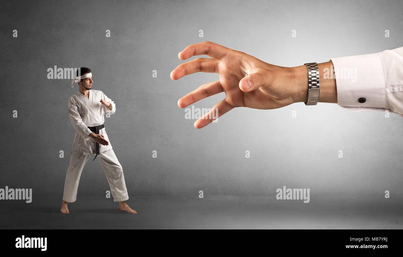 Kleine Karate Mann kämpfen mit großen Hand Stockbild