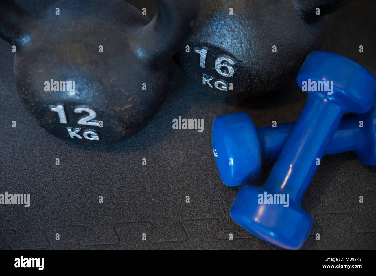 Zwei gusseisernen Kettlebells und zwei Neopren beschichteten Bügeleisen Kurzhanteln, für Muskelaufbau, Aerobic- und, auf einer schwarzen Matte positioniert Stockbild