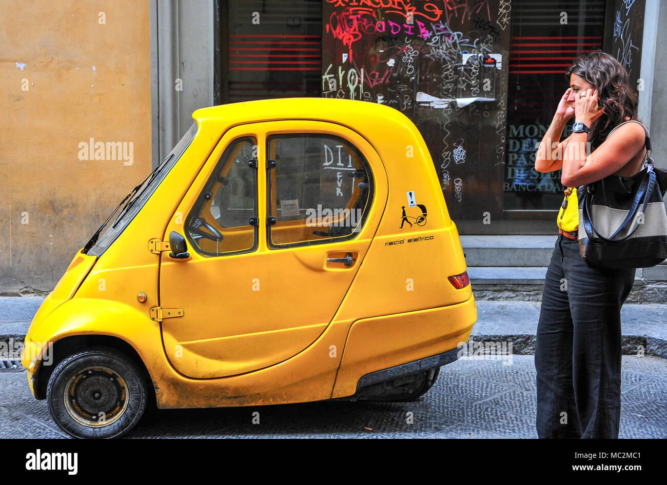 Florenz, Italien: Straßenbild, junge Frau, die in der Nähe von hellen gelben Auto, am Telefon sprechen Stockbild