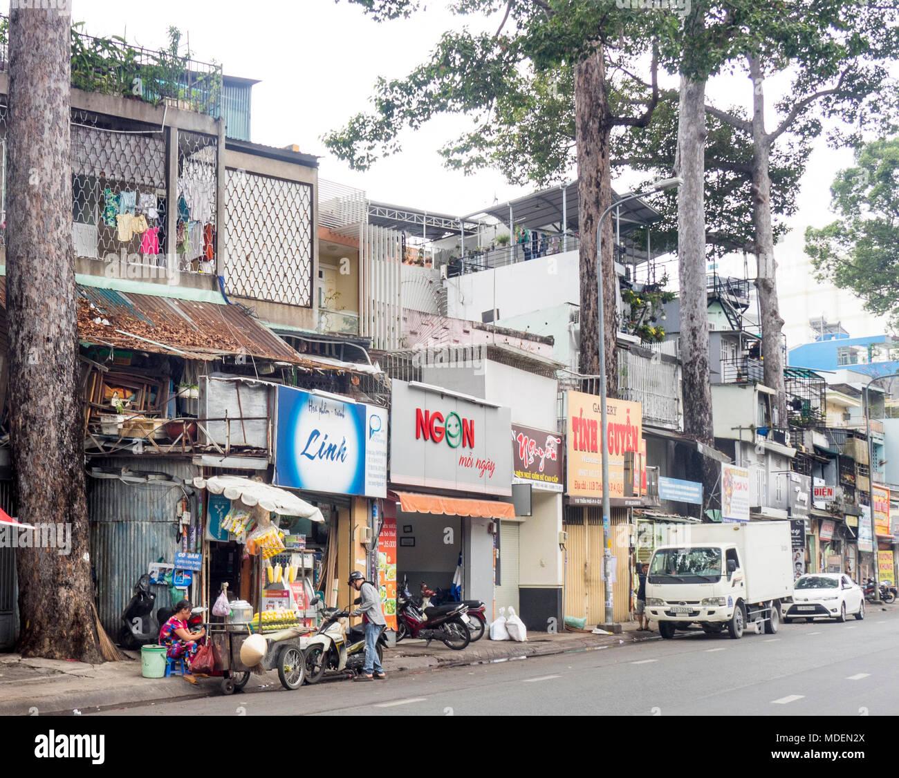 Straßenbild aus einer Reihe von Geschäftshäusern und Street Food Anbieter auf einer von Bäumen gesäumten Straße in Ho Chi Minh City, Vietnam. Stockbild