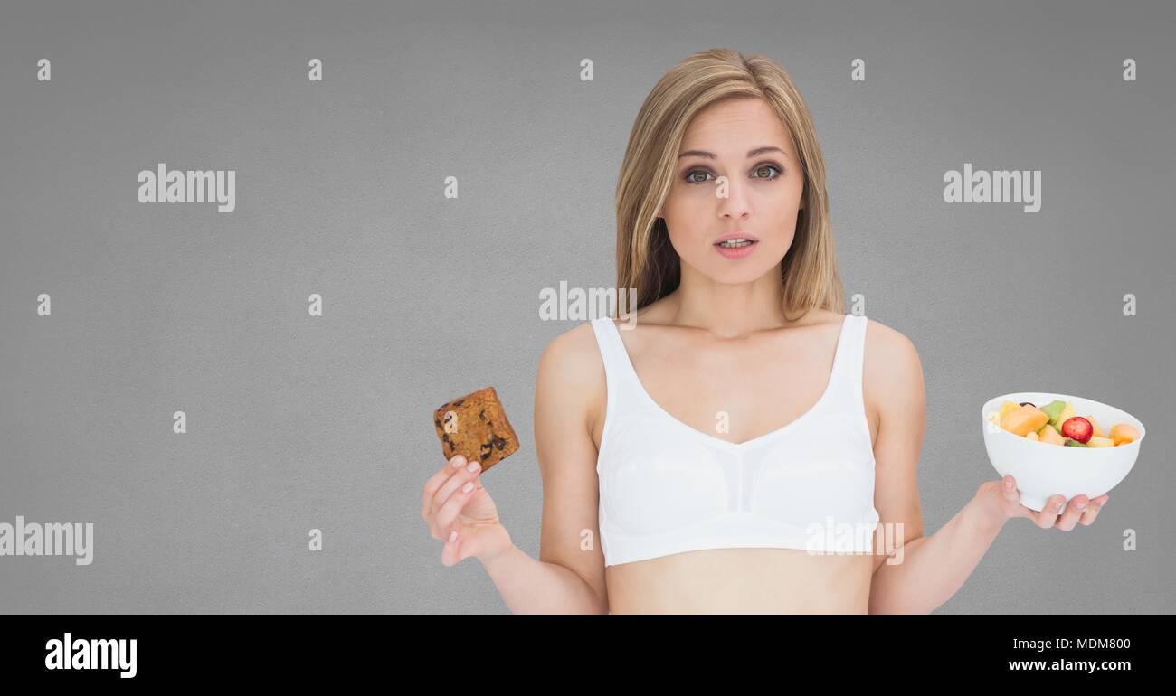 Frau mit der Entscheidung, gesundes und ungesundes Essen auswahl Stockbild