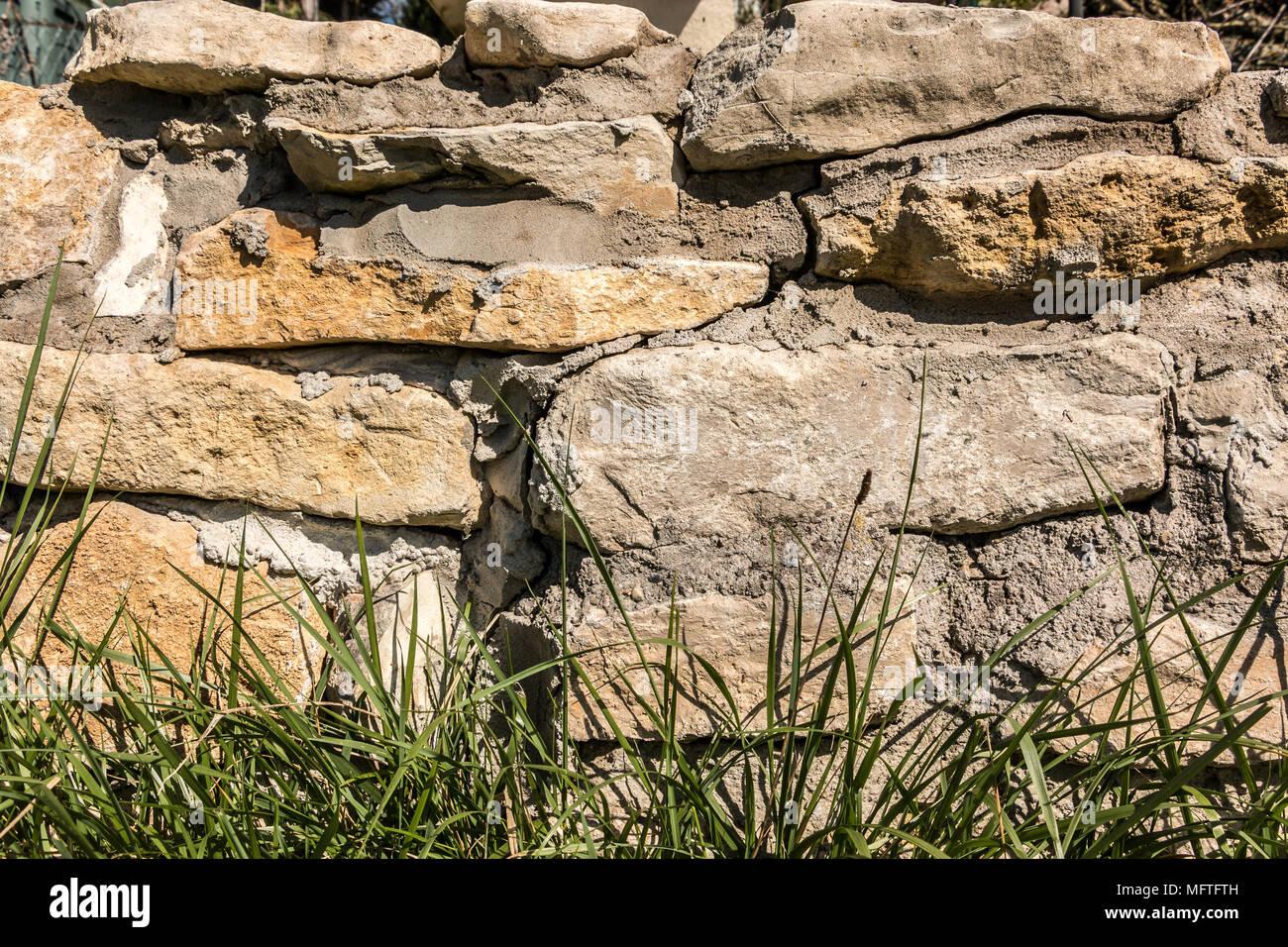 Große Mauer aus Stein im Garten Stockbild