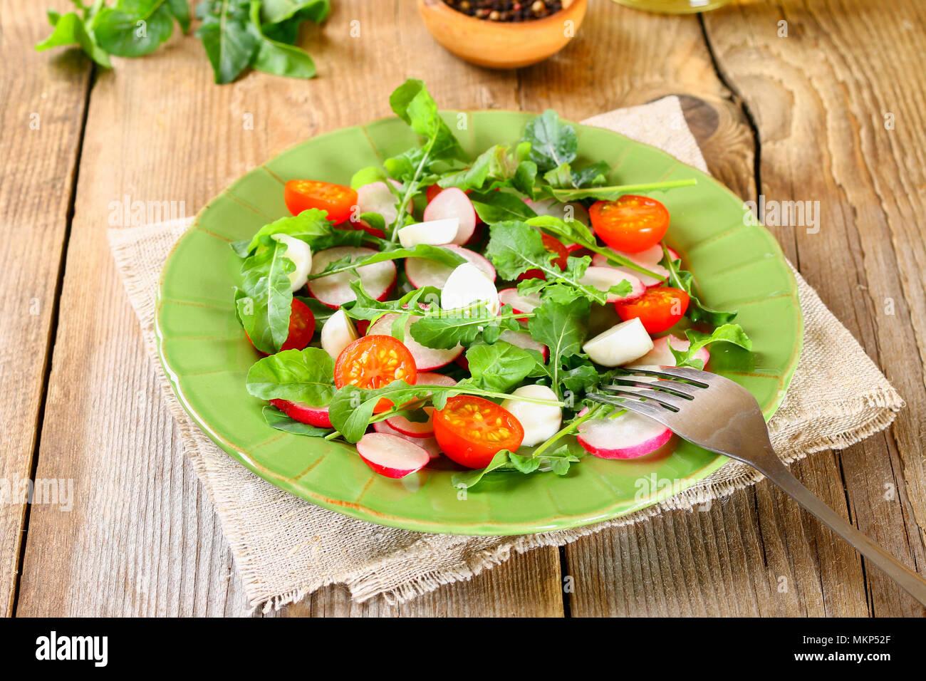 vegetarische salat mit rucola tomate radieschen und mozzarella auf einem alten holztisch. Black Bedroom Furniture Sets. Home Design Ideas