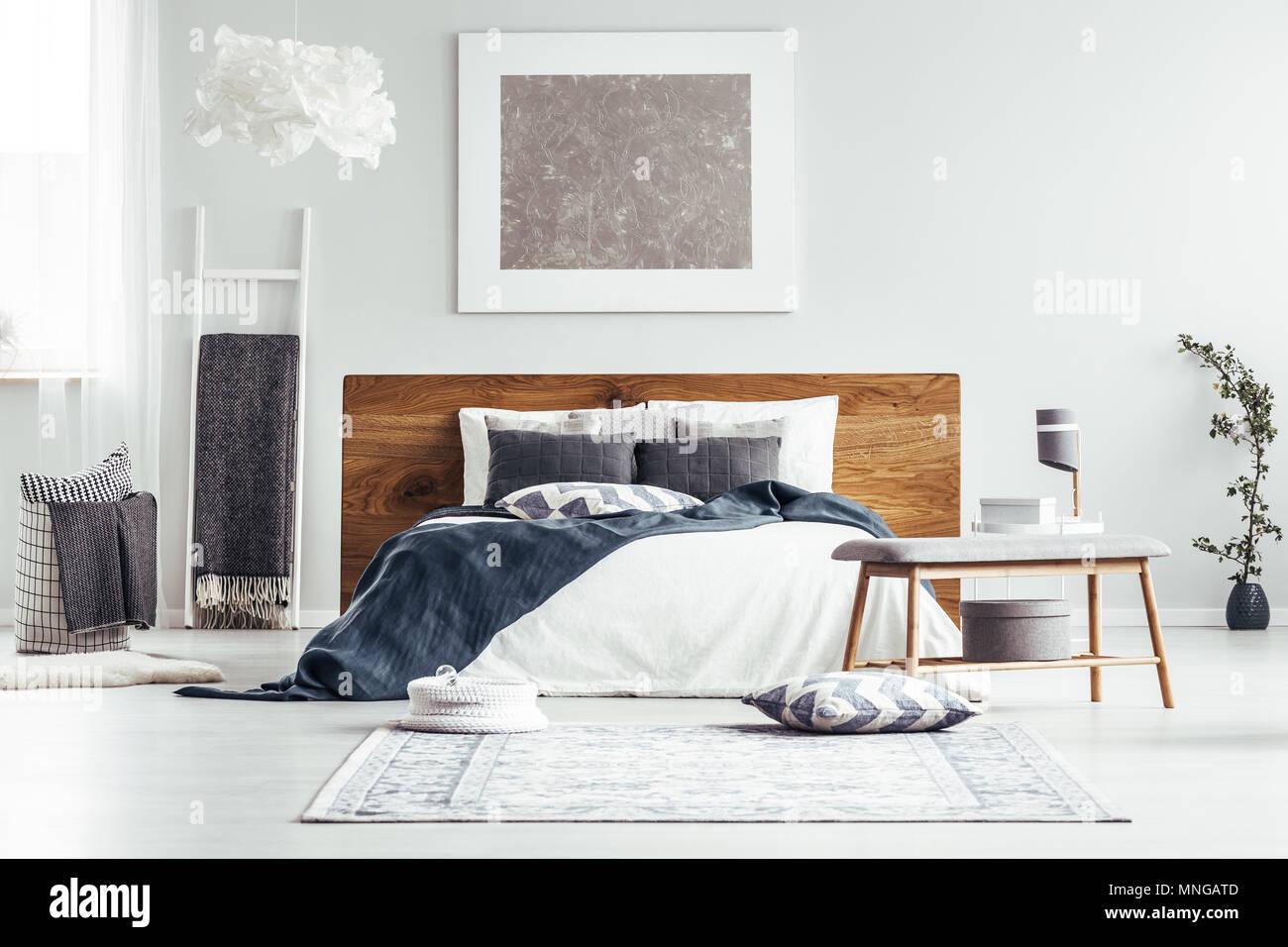 Silber Malerei auf weiße Wand über dem Bett in Designer Schlafzimmer Innenraum mit Leiter, Lampen und Bettwäsche Stockbild