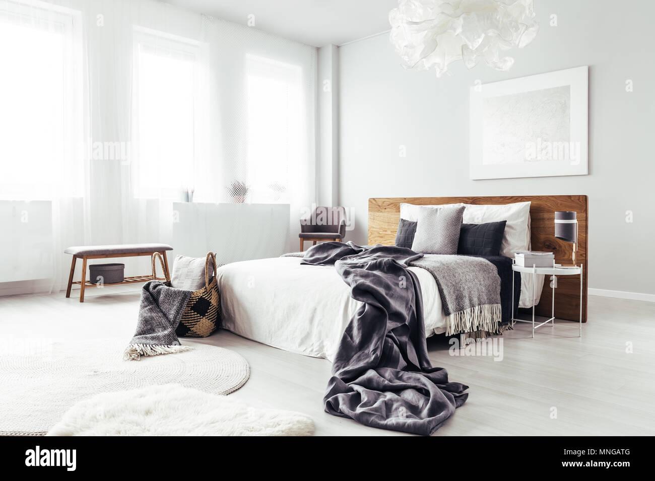 Bettwäsche auf King-Size-Bett mit hölzernen bedhead in helles Schlafzimmer mit Sitzbank und Korb Stockbild