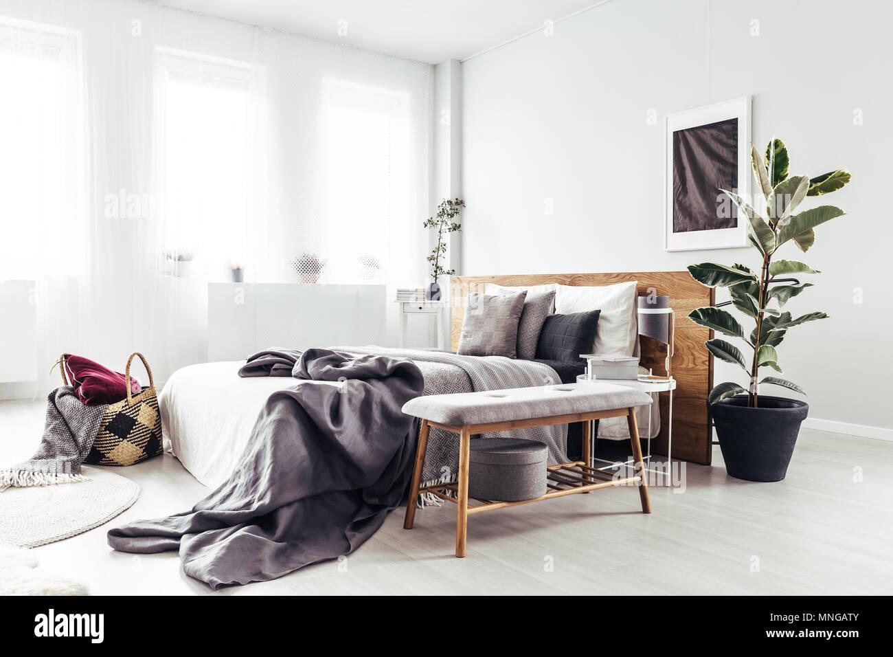 Holzbank und Anlage neben dem Bett mit grau Bettwäsche in hellen Schlafzimmer Innenbereich mit schwarzem Poster an der Wand Stockbild