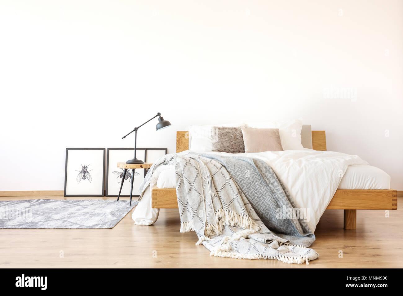 Bettwäsche auf hölzernen King-Size-Bett gegen weiße Wand im geräumigen Schlafzimmer mit Lampe auf einem Hocker Stockbild