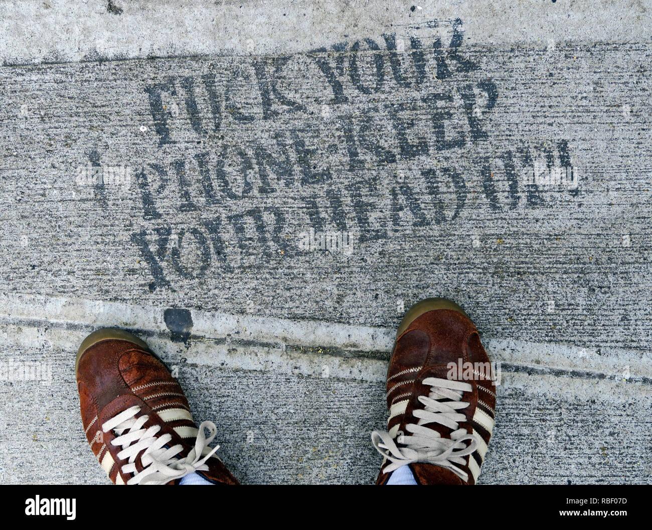 Laden Sie dieses Alamy Stockfoto Fuck Ihr Telefon, den Kopf oben, Schablone auf Pflaster, mit Füßen in Adidas Trainer, Chinatown, New York City, New York City, NY, USA - RBF07D