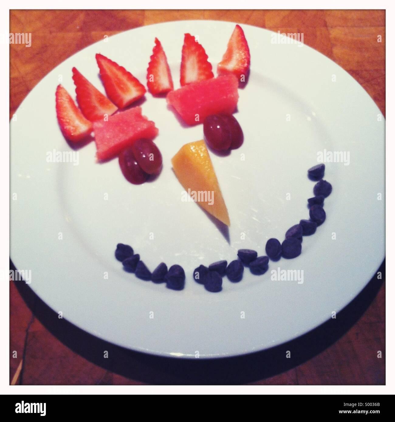 Kinderteller mit Gesicht erstellt mit Essen Stockbild