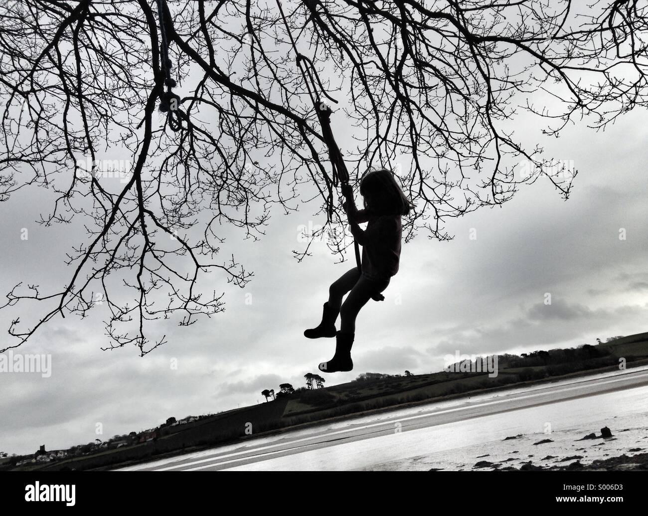 Mädchen Kind Schaukeln am Seil an einem Baum. Abenteuer am Ufer Flusses. Stockbild