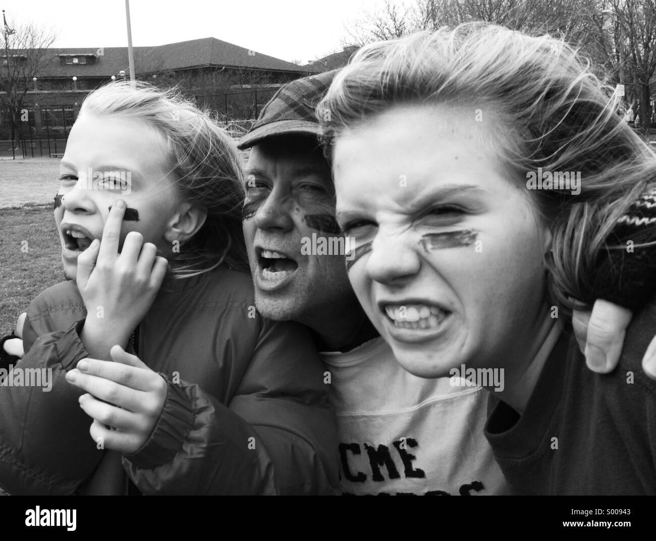 Mach dich bereit für ein Familienspiel des Fußballs, ein Vater und seine Töchter. Stockfoto