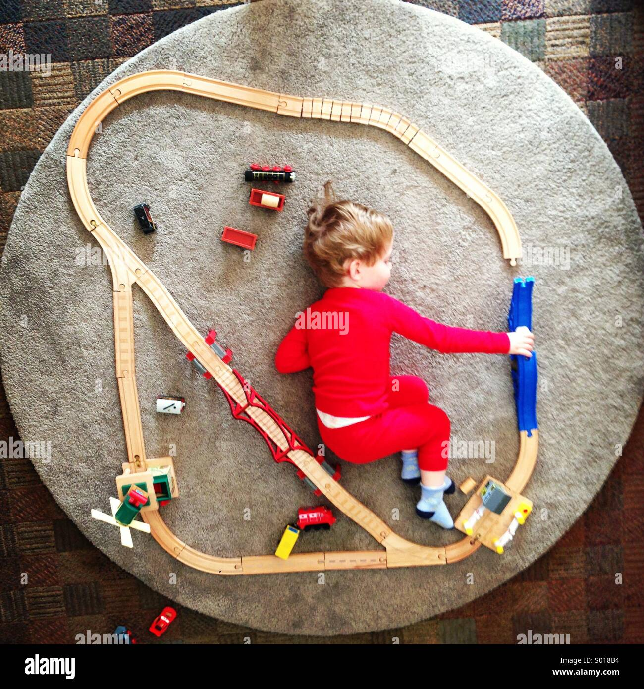 Kleiner Junge spielt mit einem Spielzeug-Bahnstrecke Stockbild