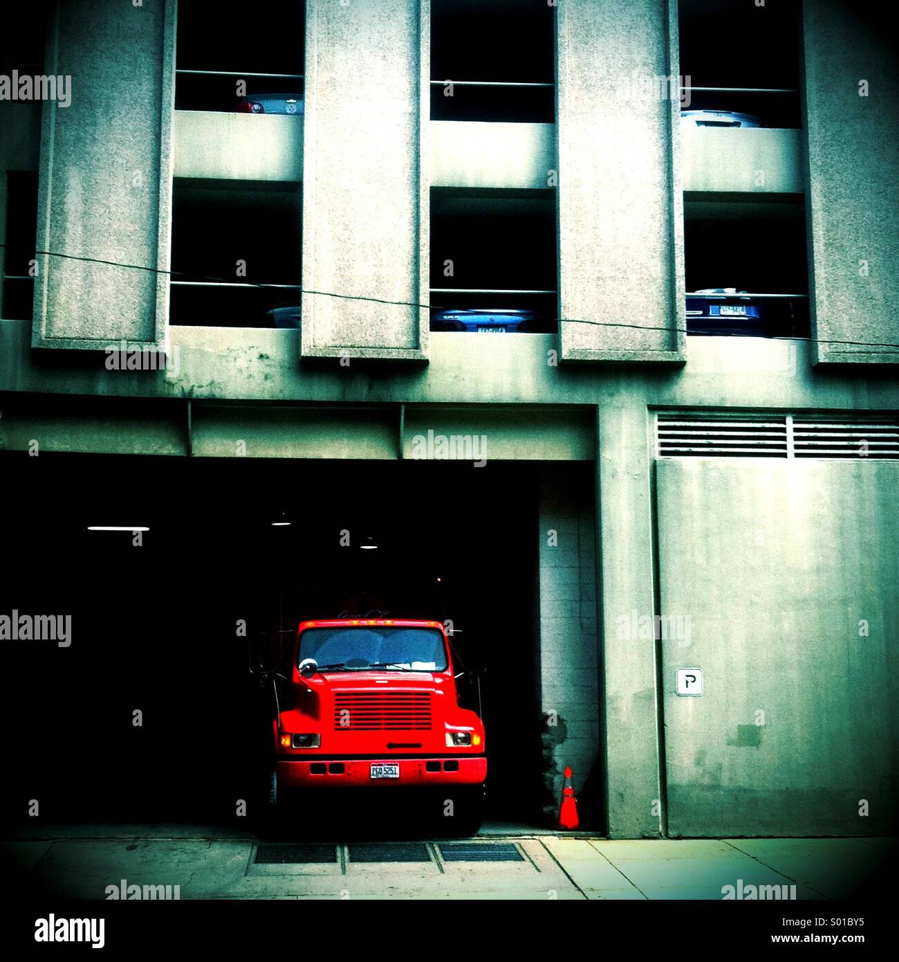 Ein rote Kipper ist in dem Eintrag zu einem Parkhaus geparkt. Stockbild