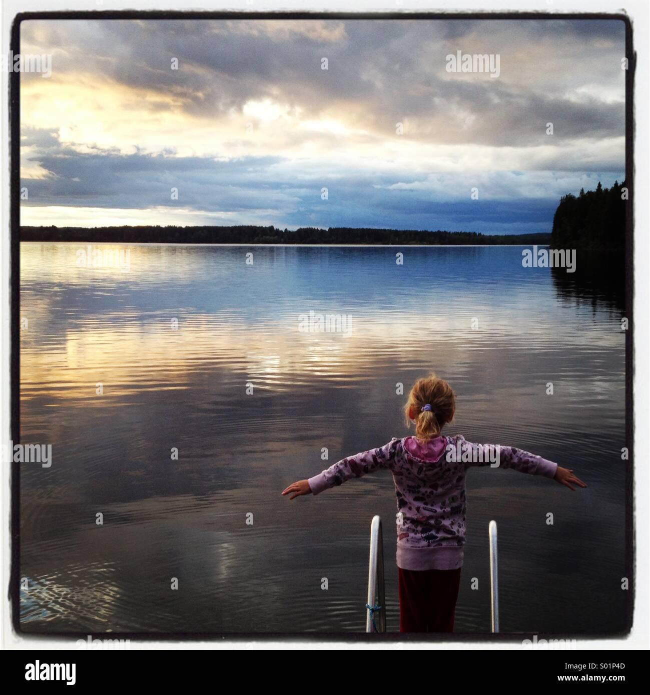Ein Mädchen steht am Ende eines Piers an einem riesigen noch See in Skandinavien Stockbild