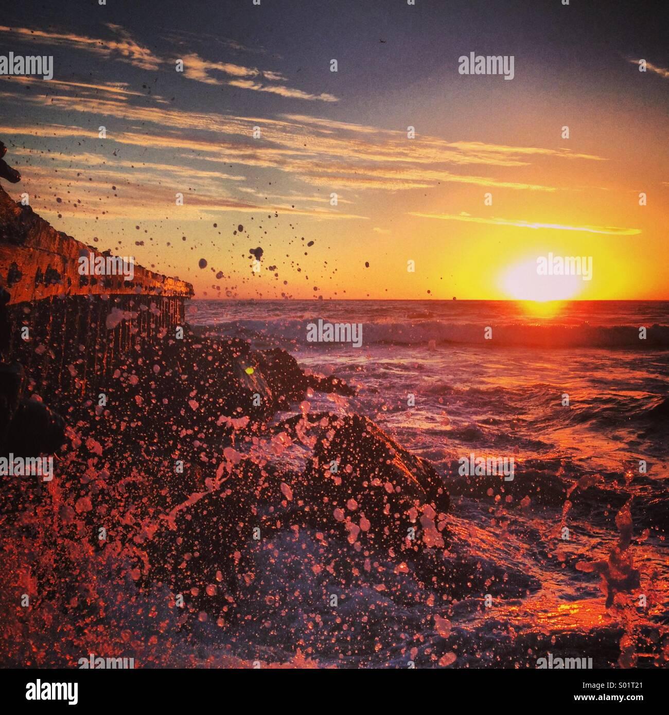 Riesige Welle auf Felsen während des Sonnenuntergangs. Stockbild