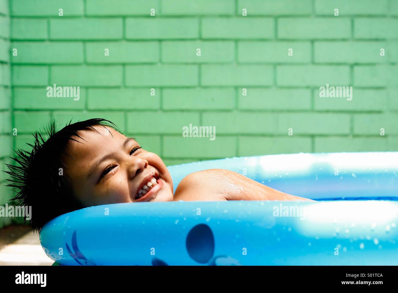 Kind in ein Kinderplanschbecken Stockbild