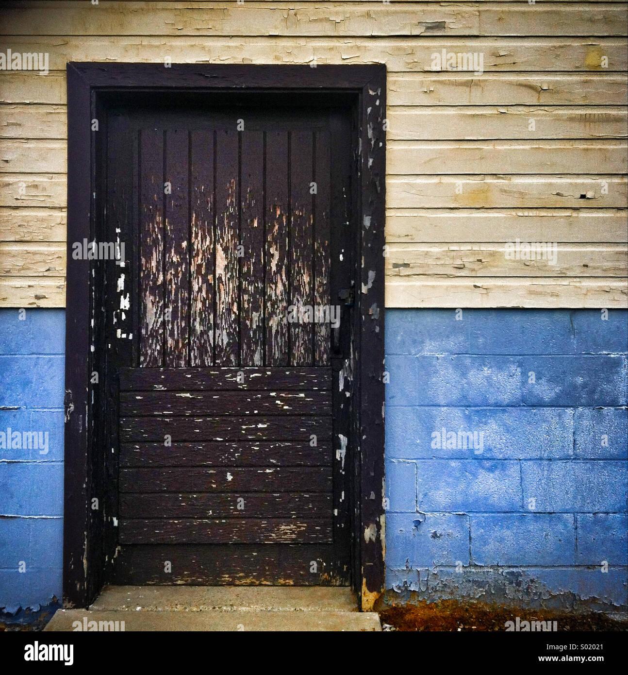 Eine braune Tür mit abblätternde Farbe auf zwei Gebäude Ton Stockbild
