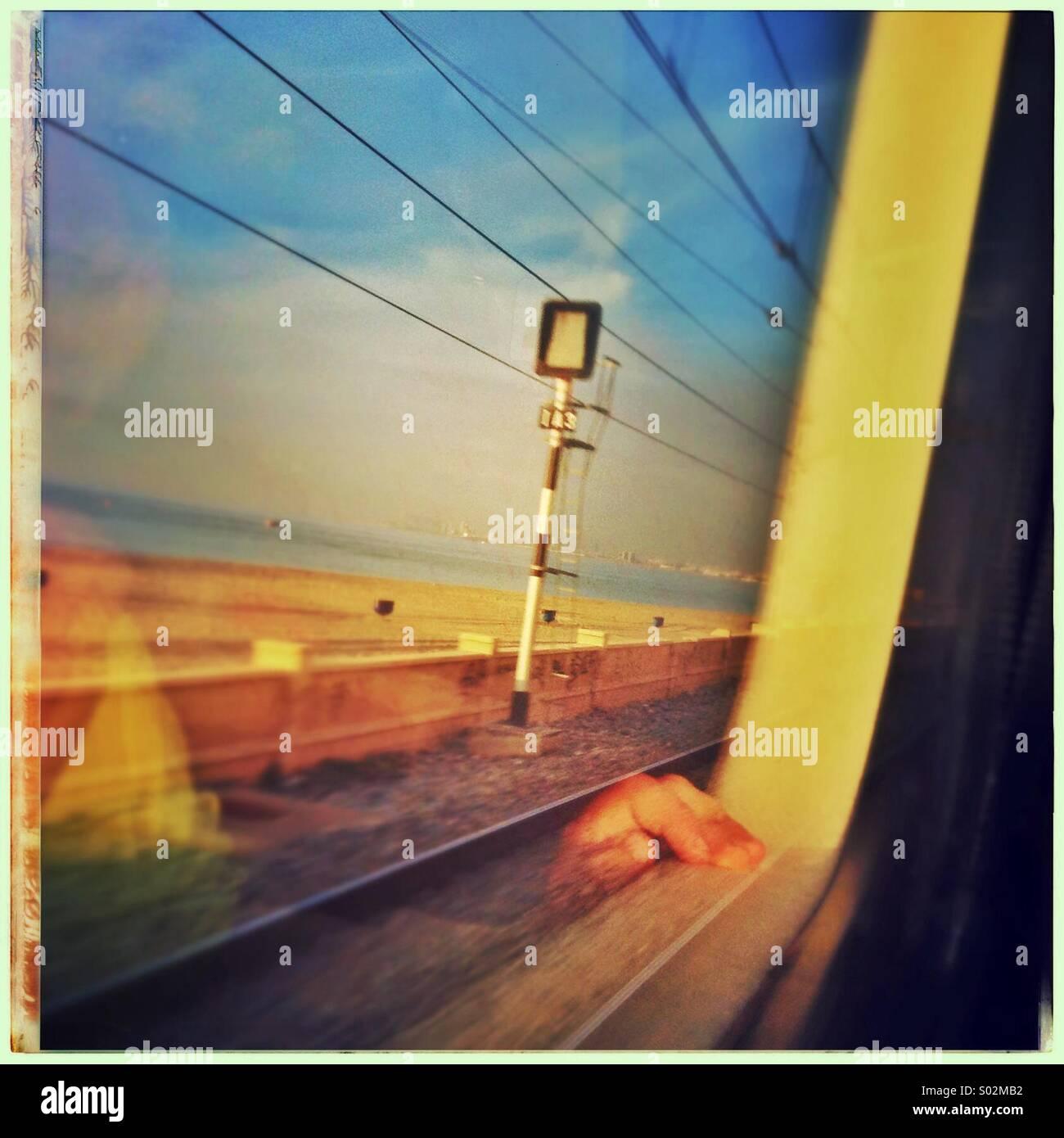 Reflexion einer Hand eines kleinen Jungen, der Blick aus dem Zugfenster im Norden von Barcelona Küste, Katalonien, Stockbild