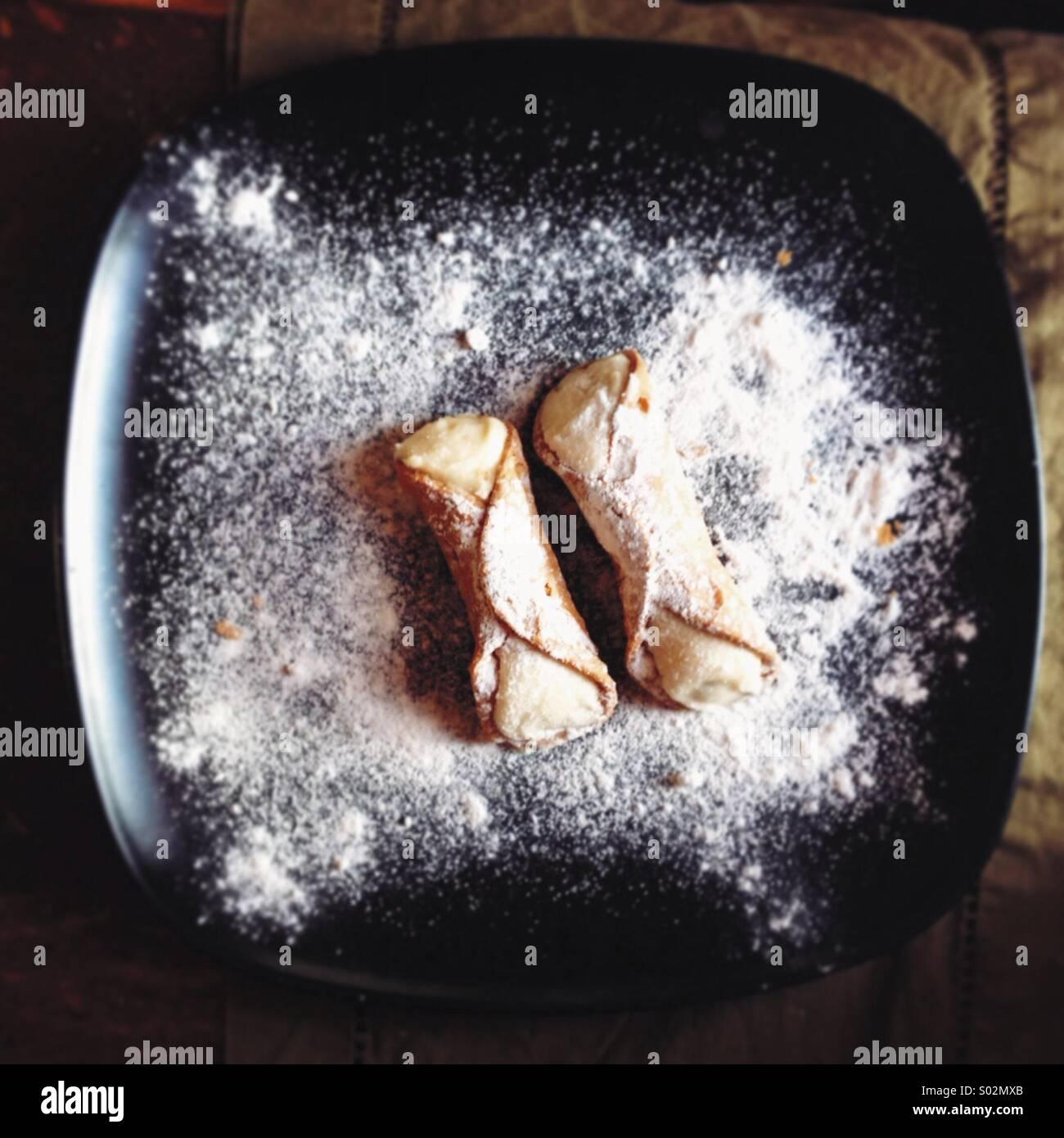 Zwei Cannoli auf einer schwarzen Platte Stockbild