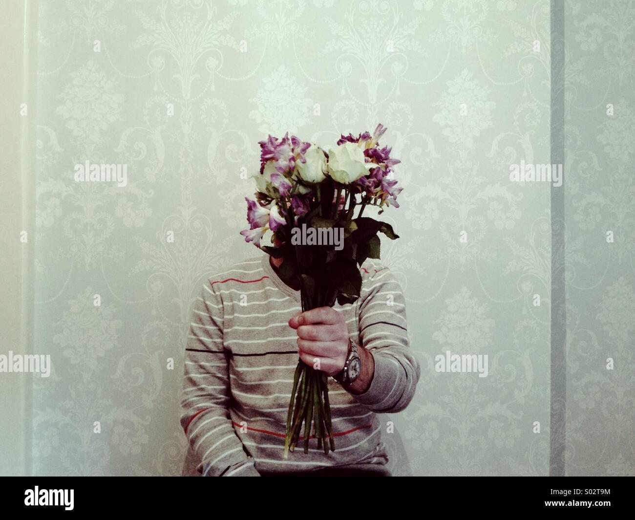 Verborgene Figur präsentiert einen Blumenstrauß im Innenbereich auf einem einfachen tapezierten Hintergrund Stockbild